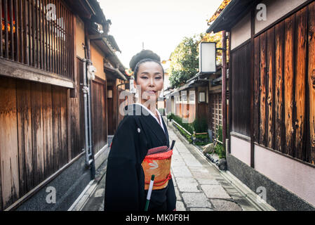 Japanese woman wearing traditional dress and walking outdoors - Stock Photo