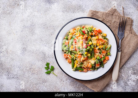 Vegetarian dish couscous with vegetables on light concrete table - Stock Photo