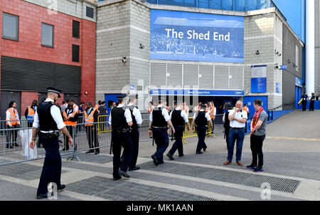 Police patrol the area before the Premier League match at Stamford Bridge, London. - Stock Photo