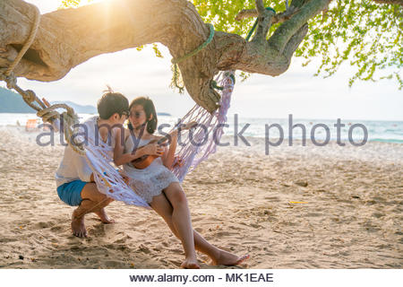 Romantic couple is sitting and kissing on sea beach on rope swing . Family vacation on honeymoon. Love and relationship - Stock Photo
