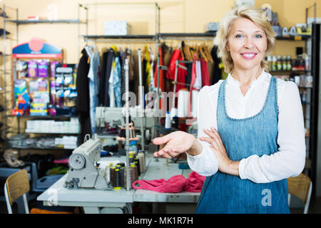 Portrait of professional smiling mature female tailor standing in sewing atelier - Stock Photo
