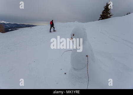Snowman with man walking in the background, Col Visentin, Belluno, Italy - Stock Photo