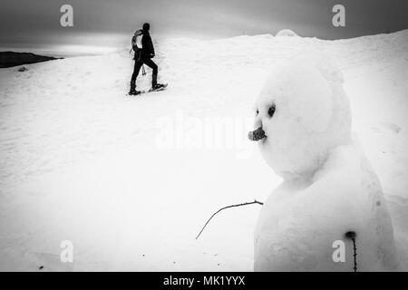 Black and white snowman with man walking in the background, Col Visentin, Belluno, Italy - Stock Photo