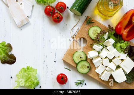 Feta cheese and black olives, cooking qreek salad with fresh vegetables on a white wooden table. - Stock Photo