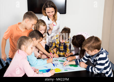 Team of elementary age children and young teacher drawing on one sheet - Stock Photo