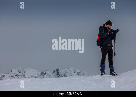 BELLUNO, ITALY - JANUARY 04, 2018:  man who takes photographs of the snow, with the Dolomite peaks in the background - Stock Photo