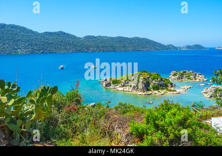 Indented coastline of Kalekoy with rocky islets, covered with greenery and washed by waters of Kekova Bay, Turkey. - Stock Photo
