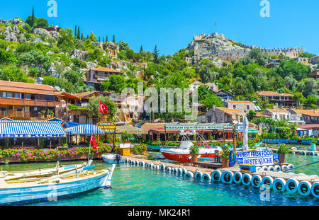 KALEKOY, TURKEY - MAY 5, 2017: The mountain village is popular tourist resort in Kekova bay with preserved Lycian tombs and Byzantine Castle among lus - Stock Photo