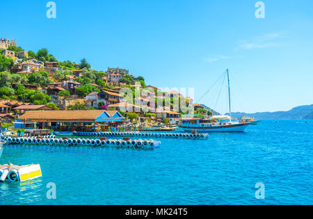 The small scenic cottages on the slope of Kalekoy village, facing the Kekova bay, Turkey. - Stock Photo