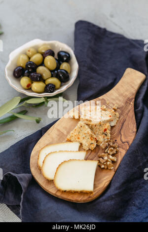 small cheese board with two different sorts of cheese on black linen and olives in seashell shaped ceramic plate. Vertical composition. - Stock Photo