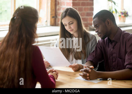 Multiracial managers reading applicant resume during hiring - Stock Photo