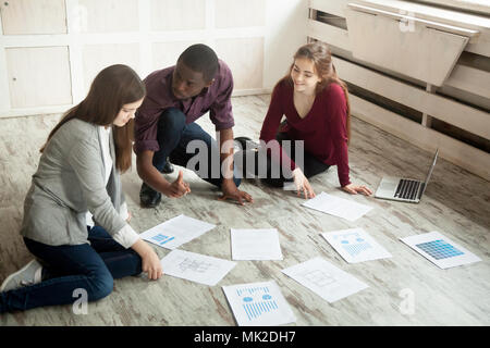 Multiracial creative team brainstorming at office floor - Stock Photo
