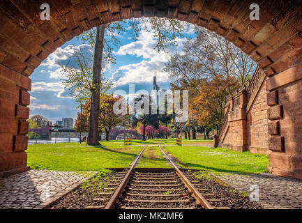 Tunnel view of Frankfurt, Germany in spring. Park with green grass, trees and blue sky. Skyscrapers in the background. - Stock Photo