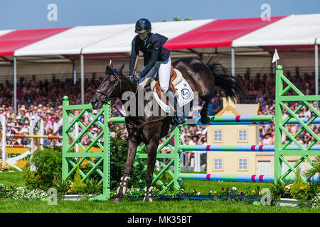 Gloucestershire, UK. 6th May, 2018. Jonelle Price (NZL) clears the last fence in the show jumping phase of the Mitsubishi Motors Badminton Horse Trials on her mount Classic Moet following her storming round of Cross Country yesterday. The smile says it all Jonelle who is married to fellow New Zealand three day eventer Tim Price had her first baby in August 2017. The couple are based near Marlborough in Wiltshire Credit: David Betteridge/Alamy Live News - Stock Photo