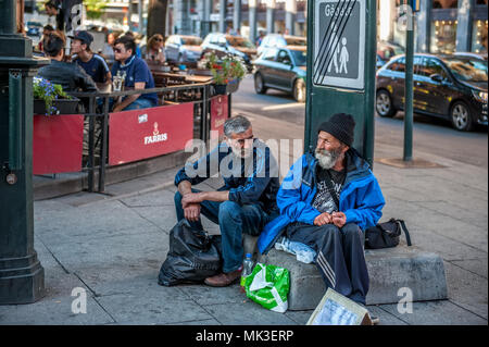 Norway, Oslo August 01 2013. Two elderly men ask for alms, sitting on the street in front of the cafe. The concept of indifference of the state to the - Stock Photo