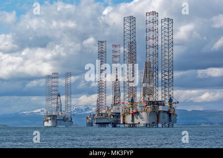 CROMARTY FIRTH SCOTLAND GROUP OF TALL STRUCTURED OIL RIGS UNDERGOING REPAIR LYING OFF CROMARTY VILLAGE WITH SNOW COVERED HILLS