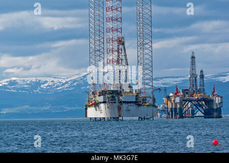 CROMARTY FIRTH SCOTLAND TALL OIL RIG OR DRILLING PLATFORM BAUG AND DECOMMISSIONED OIL RIG WITH SNOW COVERED HILLS - Stock Photo