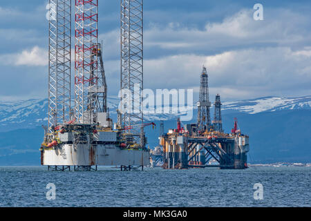 CROMARTY FIRTH SCOTLAND TALL OIL RIG OR DRILLING PLATFORM BAUG WITH DECOMMISSIONED OIL RIG AND SNOW COVERED HILLS
