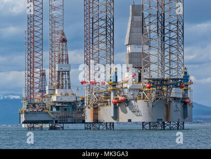 CROMARTY FIRTH SCOTLAND TALL STRUCTURED OIL RIG OR DRILLING PLATFORM BAUG  LYING OFF CROMARTY VILLAGE WITH SNOW COVERED HILLS