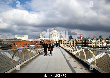 London, UK: February 25, 2018: Tourists cross the Millennium Bridge linking the City of London with Bankside between St Paul's Cathedral and the Tate - Stock Photo