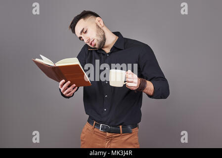 Portrait of young handsome man with phone, cup of coffe and book on hands. The concept of overtime, stress and a lot of work - Stock Photo