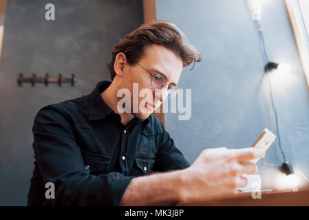 Close-up of man received good news on smart phone, Man resting in cafe and texting new mail messages, blurred background, shallow DOF - Stock Photo