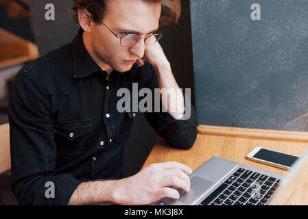 Creative man designer working on his laptop computer while waiting to orders at his favorite cafe indoors, male student working on net-book during morning breakfast in modern coffee shop interior - Stock Photo