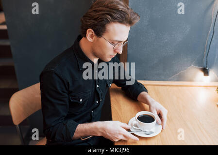Handsome bearded man in checked shirt holding fork eating in cafe and smiling - Stock Photo