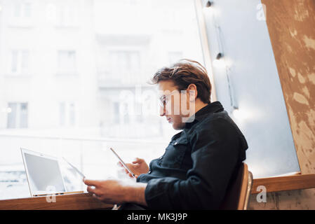 Relaxed young professional surfing the Internet on his laptop in a cafe - Stock Photo