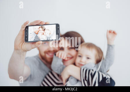 family, holidays, technology and people - smiling mother, father and little girl making selfie with camera over white background - Stock Photo