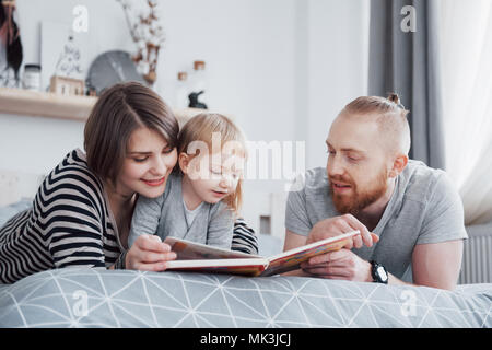 Father, Mother and Little Daughter Reading Children's Book on a Sofa in the Living Room. Happy big family read an interesting book on a festive day. Parents love their children - Stock Photo