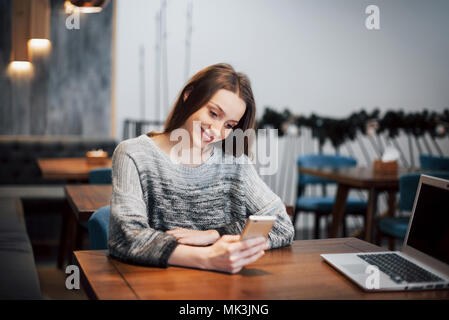 an attractive girl with long black hair ponders a new project during a coffee break sitting at a table in a coffee shop - Stock Photo