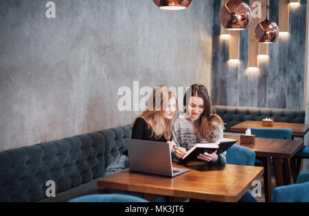 One-on-one meeting.Two young business women sitting at table in cafe.Girl shows colleague information on laptop screen.Meeting friends, dinner together.Teamwork, business meeting. Freelancers working - Stock Photo