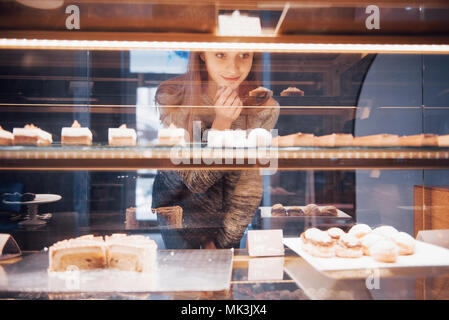 Smiling woman at camera through the showcase with sweet and cakes in modern cafe interior - Stock Photo