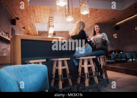 Toned picture of best friends having date in cafe or restaurant. Beautiful girls talking or communicating while drinking coffee - Stock Photo