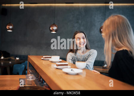 Two girl friends drinking coffee in the cafe - Stock Photo