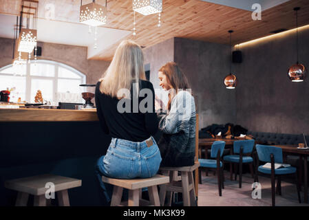Two smiling friends reading funny online chat on modern telephone sitting with tasty coffee in restaurant.Hipster girls enjoying recreation time in cafe with hot beverages and messaging on cellular