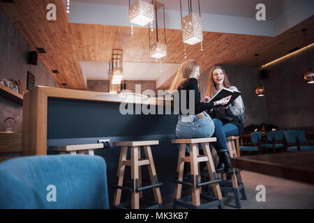 Two young women sitting in the cafe drinking coffee and enjoying in good books. Students on coffee break. Education, lifestyle concept - Stock Photo