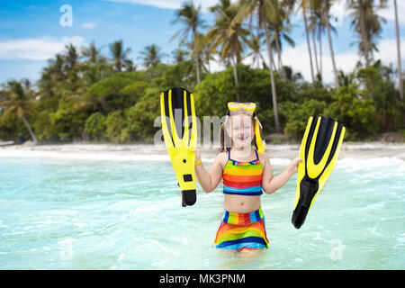 Child with swim fins snorkeling on tropical ocean beach with palm trees. Little girl diving on exotic island in Asia. Summer sea vacation for family w - Stock Photo