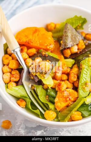 Salad with baked pumpkin and chickpeas with mustard-honey dressing in a white plate. Healthy vegan food concept. - Stock Photo