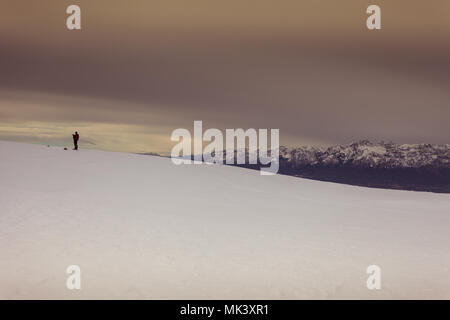 Man who takes photographs of the snow, with the Dolomite peaks in the background, Col Visentin, Belluno, Italy - Stock Photo