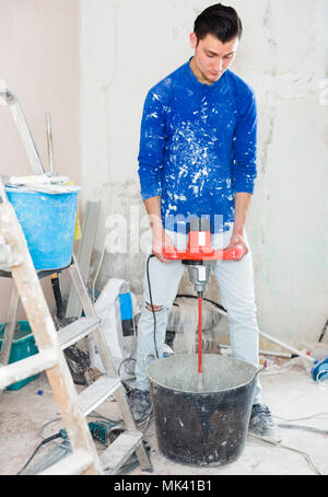 builder mixing plaster in bucket using electric mixer in repairable room - Stock Photo