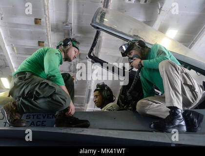 "171101-N-XU691-151 INDIAN OCEAN (Nov. 1, 2017)  Marines perform a functions check for the onboard oxygen generating system of an F/A-18C Hornet assigned to the ""Death Rattlers"" of Marine Fighter Attack Squadron (VMFA) 323 aboard the aircraft carrier USS Nimitz (CVN 68). The ship and its carrier strike group is on a deployment in the U.S. 7th Fleet area of operations in support of maritime security operations and theater security cooperation efforts. (U.S. Navy photo by Mass Communication Specialist Seaman David Claypool/Released) - Stock Photo"