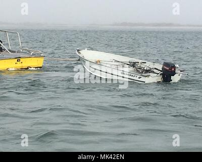 A disabled 14-foot boat is put into a tow by a commercial salvage company near Moriches, New York, November 3, 2017. A Coast Guard boatcrew rescued three people after the vessel became disabled and took on water near the Moriches Inlet. (U.S. Coast Guard Photo by Petty Officer 2nd Class Christopher Geiser) - Stock Photo