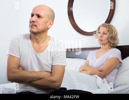 Frustrated mature wife and husband having conflict in bedroom - Stock Photo