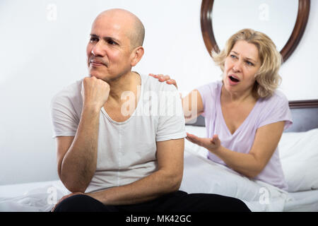 Frustrated mature man and his angry wife sorting out relationships in bed - Stock Photo