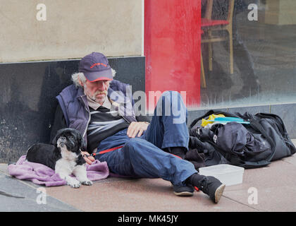 Homeless man with a dog sitting on a street in the  Buchanan Street Glasgow Scotland - Stock Photo