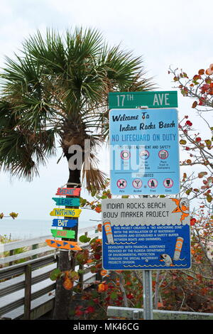 Indian Rocks, Florida city park entrance with walkway and directional signs at entrance on overcast Fall day with ocean in background. - Stock Photo