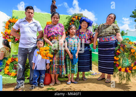 Santiago Sacatepequez, Guatemala - November 1, 2017: Indigenous family dressed in traditional clothing in cemetery on All Saints' Day. - Stock Photo
