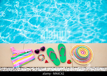 Swimming pool accessories flat lay. Top view of beach items on pool deck. Flip flops, bikini and hat, sun glasses. Water toys. Summer vacation in trop - Stock Photo
